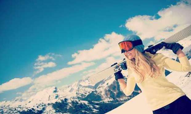 Blue sky with clouds over a snow-capped mountain with a woman carrying a ski on her shoulders. Explore Andorra Hen Party ideas below: