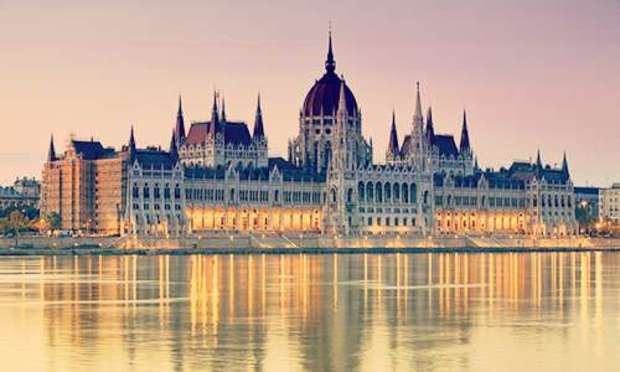 Pink skies over the Budapest Parliament Building with lights shining off the river. Explore Budapest Hen Party ideas below: