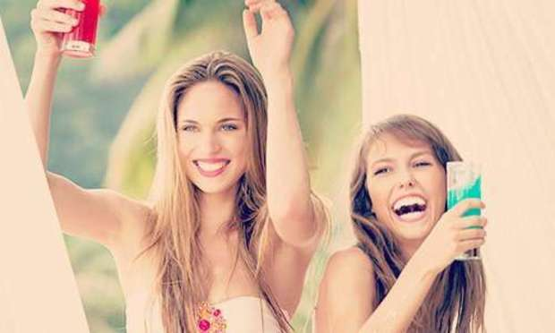 Two girls drinking and dancing with cocktails. Discover Calvia Beach Hen Party ideas below: