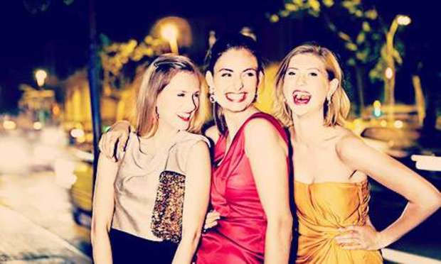 Girls smiling and laughing on a night out wearing beige, yellow and red. Discover Italy Hen Party ideas below: