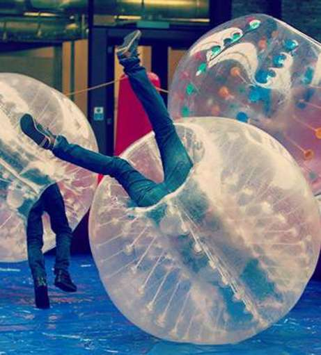 People playing bubble football, going head over feet. Get a Lincoln Co
